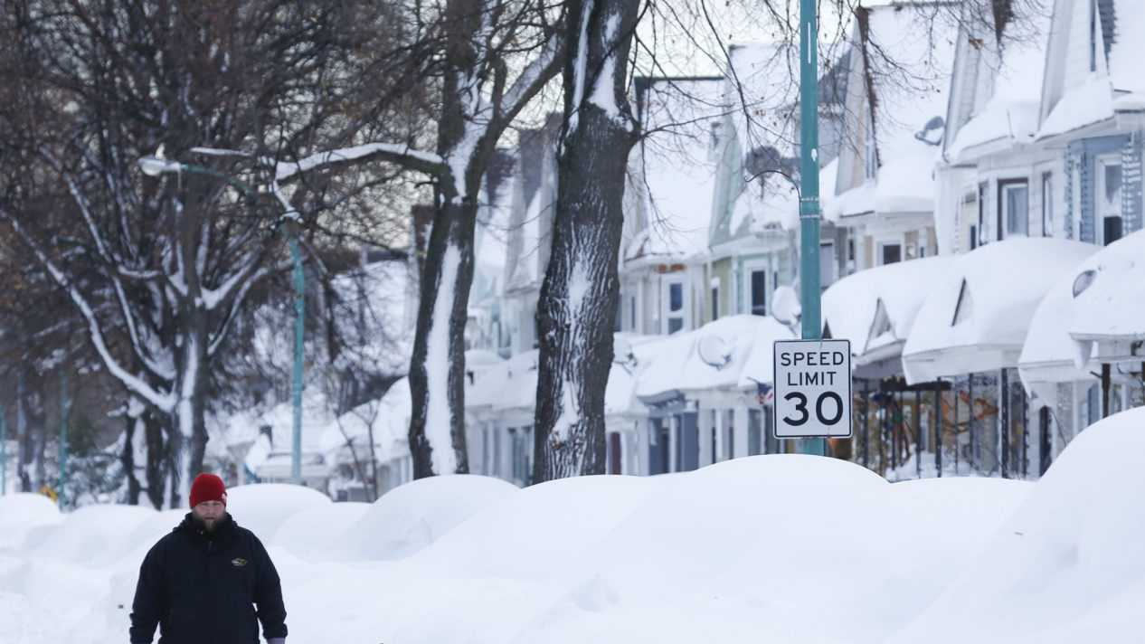 Chris Weiglein walks along his snow-bound south Buffalo neighborhood on Thursday, Nov. 20, 2014, in Buffalo, N.Y.