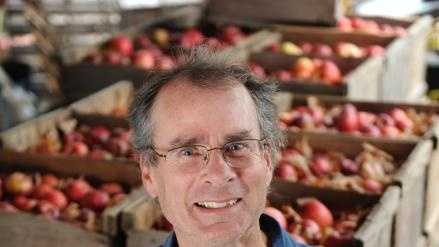 Russell Powell Holds a Northern Spy apple as he stands with crates of the fruit at Clarkdale Fruit Farm in Deerfield.