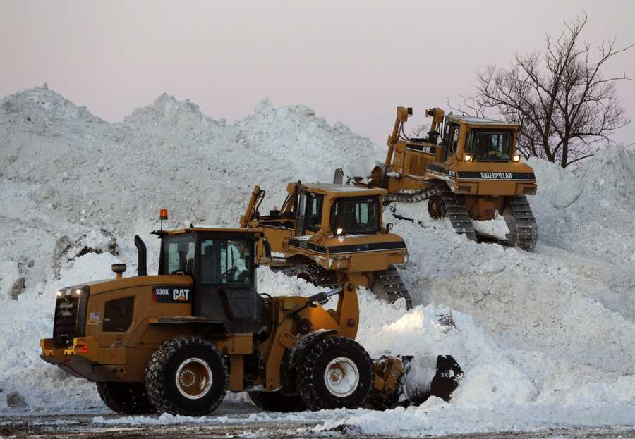 Heavy equipment moves snow at the Central Terminal that was removed from south Buffalo neighborhoods after heavy lake-effect snowstorms on Friday, Nov. 21, 2014, in Buffalo, N.Y.