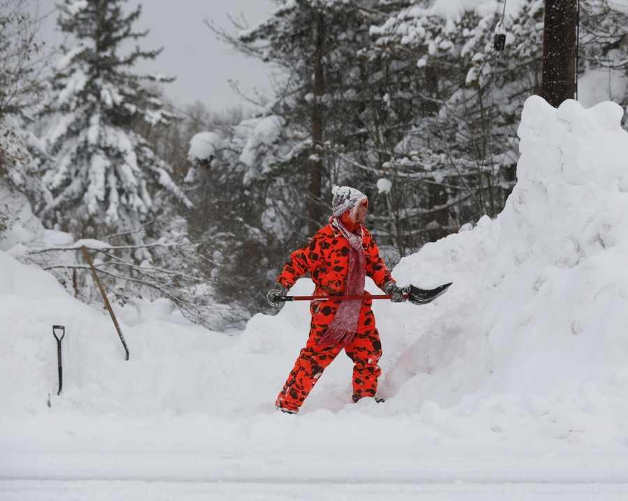 Karen McRae clears snow from her driveway on Thursday, Nov. 20, 2014, in West Seneca, N.Y.