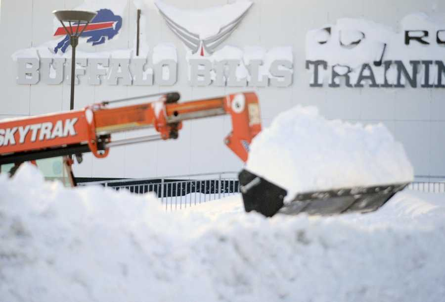 Snow is cleared alongside the Buffalo Bills training facility at Ralph Wilson Stadium in Orchard Park, N.Y. Friday, Nov. 21, 2014.