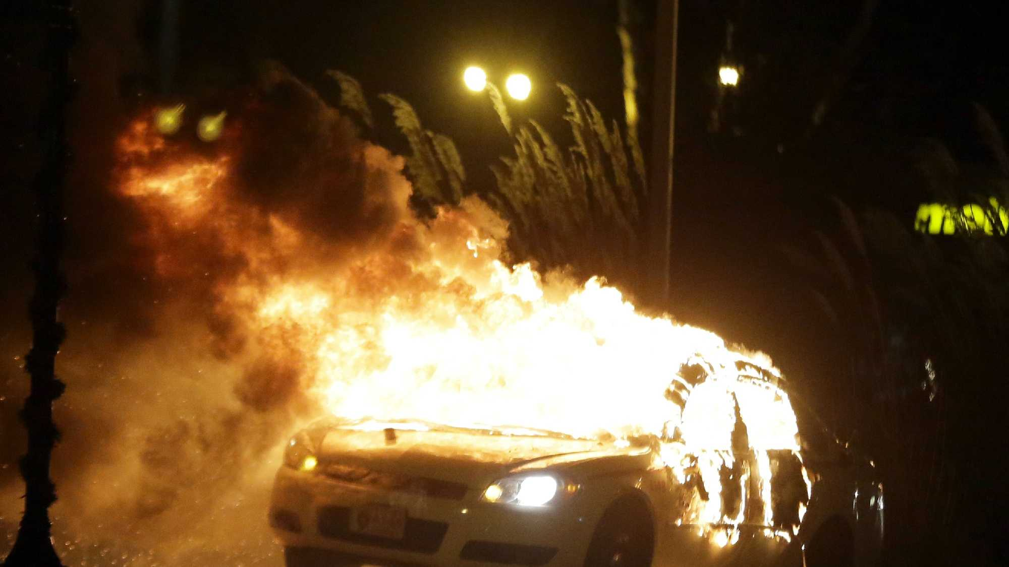 A police car is set on fire after a group of protesters vandalize the vehicle after the announcement of the grand jury decision Monday, Nov. 24, 2014, in Ferguson, Mo.