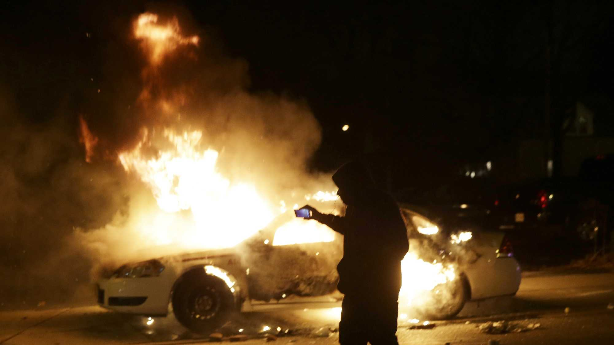 A man runs from a police car that is set on fire after a group of protesters vandalize the vehicle after the announcement of the grand jury decision Monday, Nov. 24, 2014, in Ferguson, Mo.