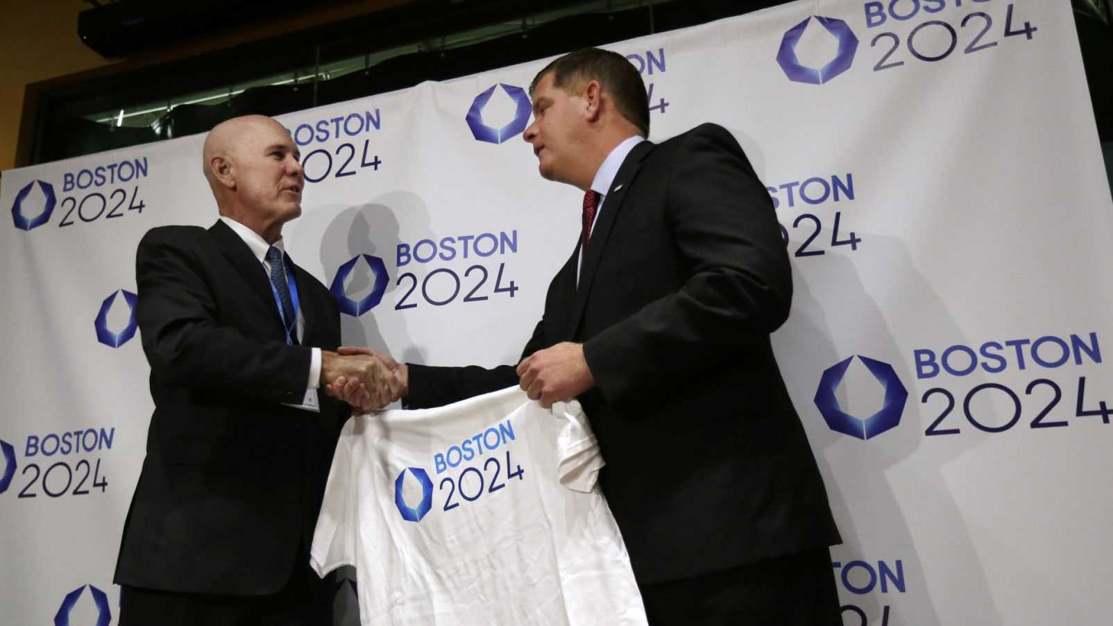 Boston Mayor Marty Walsh, right, is presented with a tee shirt by Ralph Cox, an organizer pursuing an Olympics bid, during an event held to generate public interest in a 2024 Olympics bid for the city of Boston, Monday, Oct. 6, 2014, in Boston. The U.S. Olympic Committee is weighing whether to put in a bid for the 2024 Summer Games.