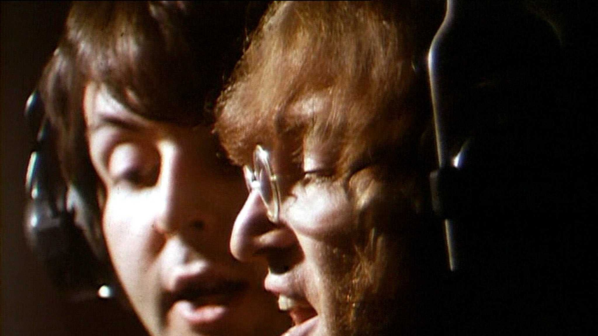 Beatles John Lennon and Paul McCartney sing their harmonizing vocal lines in the Abbey Road Studios in London, England, Feb. 11, 1968, during a recording session.