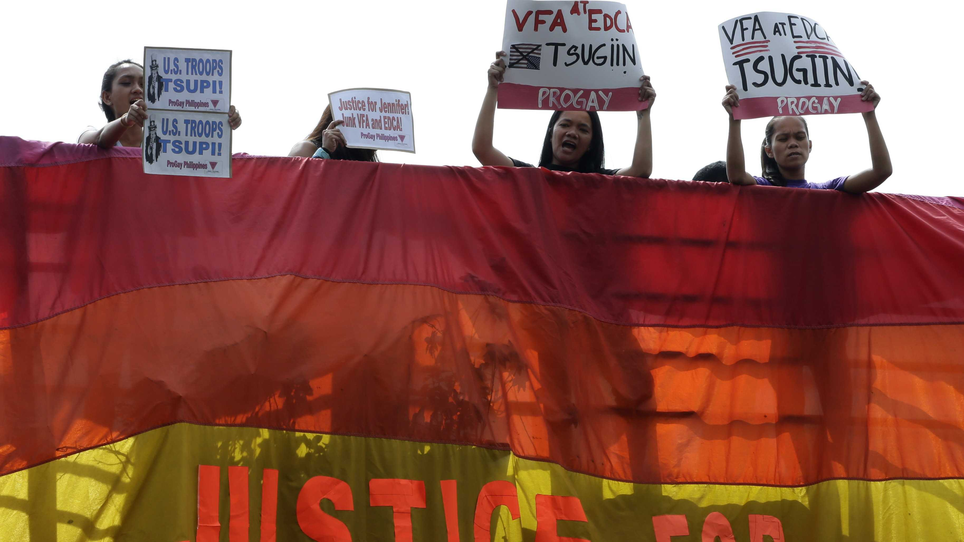 Protesters hang a rainbow banner from the foot bridge near the U.S. Embassy to demand justice for the Oct. 11, 2014 killing of Filipino transgender Jennifer Laude at the former US naval base of Subic northwest of Manila, Monday, Dec. 1, 2014.