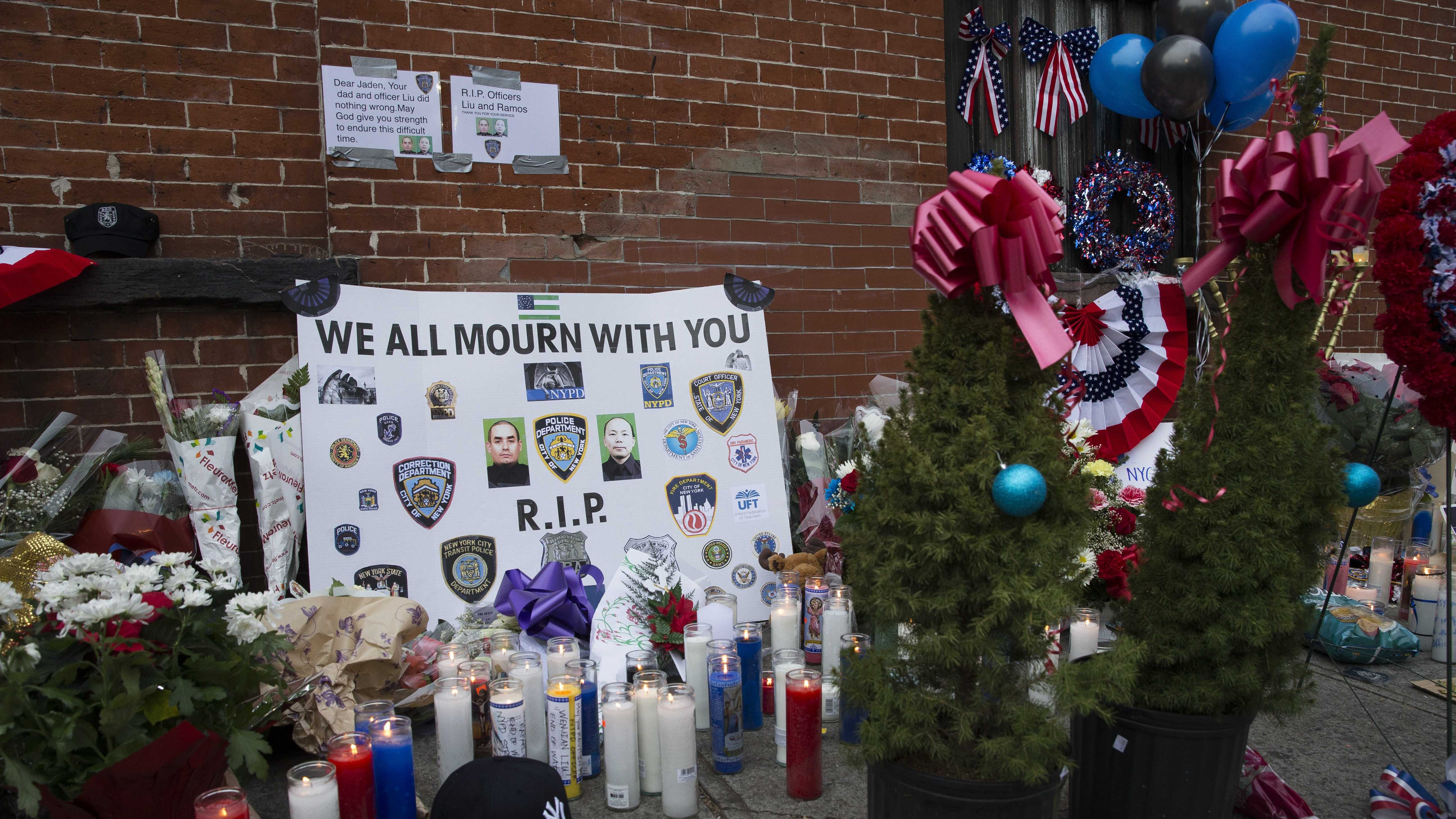 Christmas trees rest on the pavement at a makeshift memorial near the site where New York Police Department officers Rafael Ramos and Wenjian Liu were murdered in the Brooklyn borough of New York, Monday, Dec. 22, 2014.