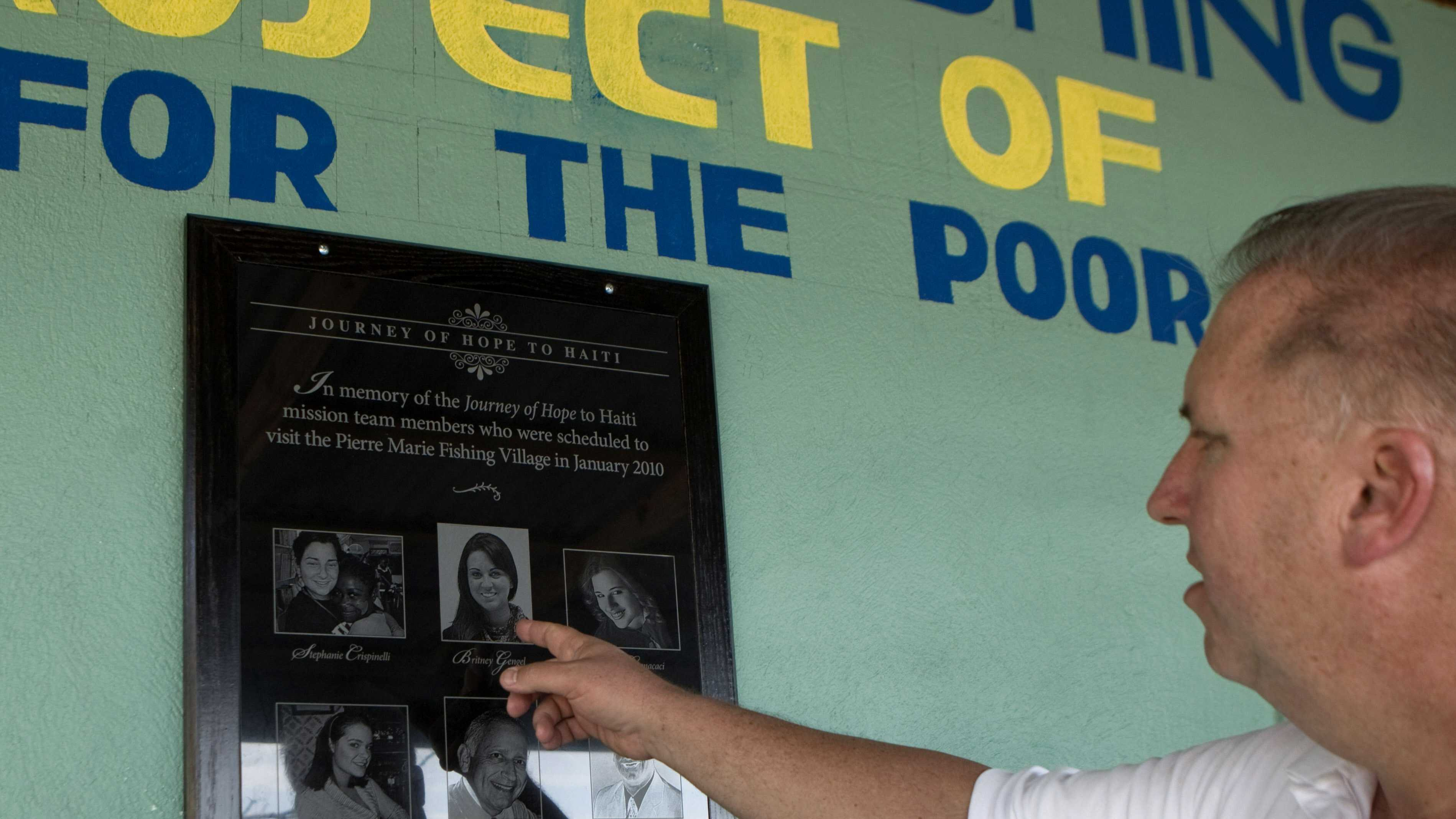 In this picture taken on Dec. 21, 2011, Massachusetts home builder Leonard Gengel points to a picture of his daughter Britney on a plaque in memory of those who died in the 2010 earthquake in Grand Goave, Haiti.