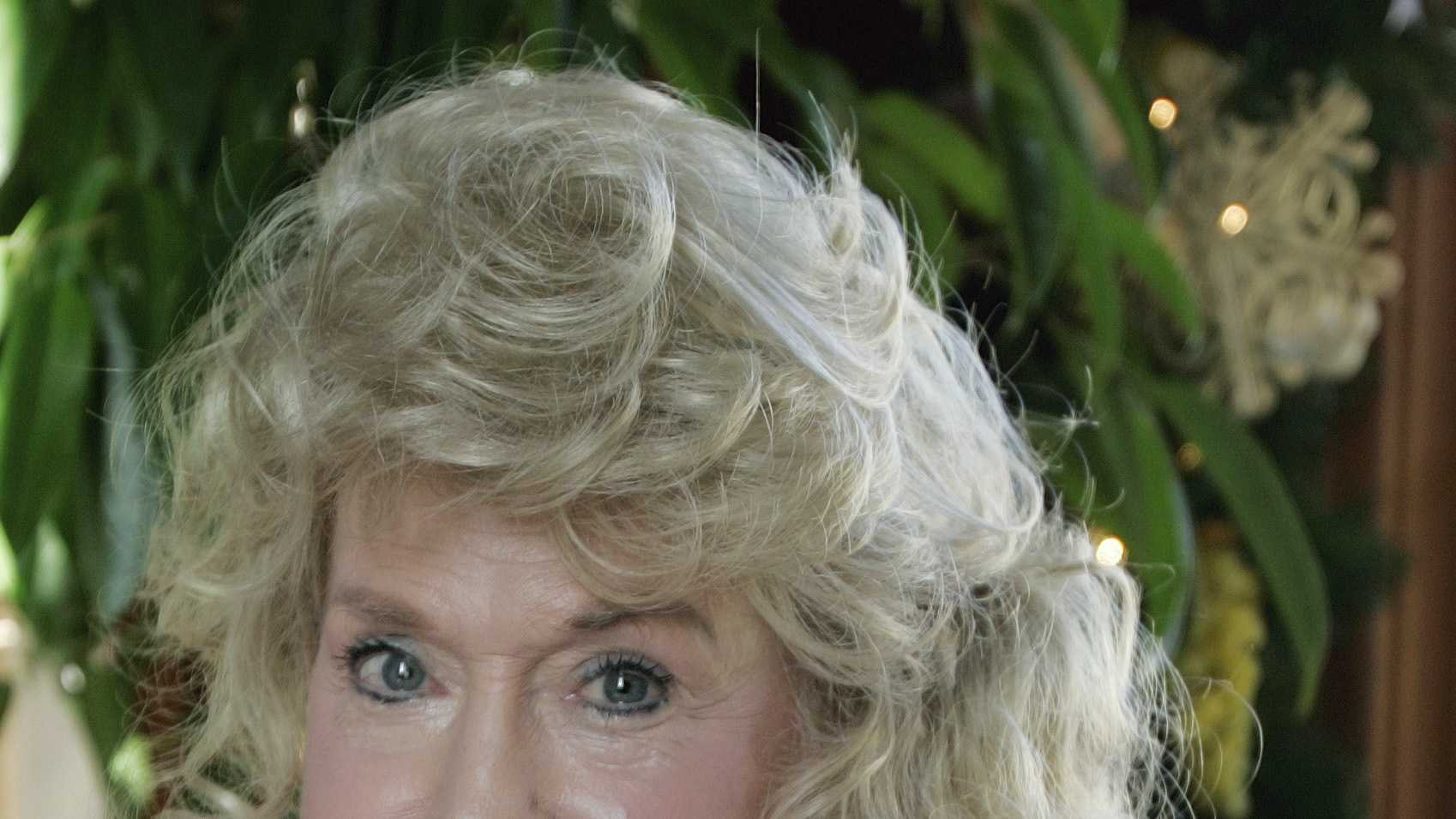 "This photo taken Jan. 8, 2009 shows Donna Douglas, who starred in the television series ""The Beverly Hillbillies"" posing for a photograph in the photo taken in Baton Rouge, La. Douglas is holding a publicity photo taken during the shooting of the TV series."