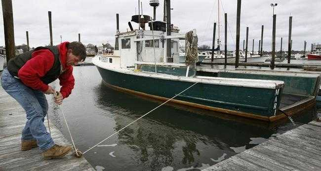 Marshfield lobsterman Don Hebert secures his boat Marianne on Monday, Jan. 26, 2015, in Green Harbor in preparation for the blizzard expected to hit Monday night