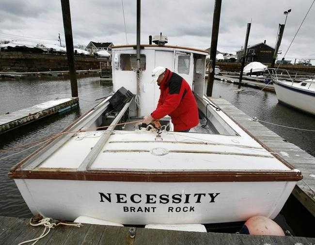 Marshfield lobsterman Wayne Marshall ties extra lines on his boat Necessity on Monday, Jan. 26, 2015, in Green Harbor in preparation for the blizzard expected to hit Monday night.