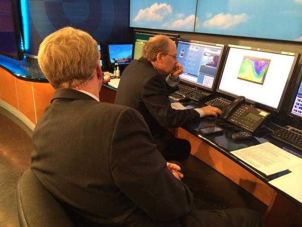 Mike Wankum looks on as Harvey Leonard gets late details on the forecast.