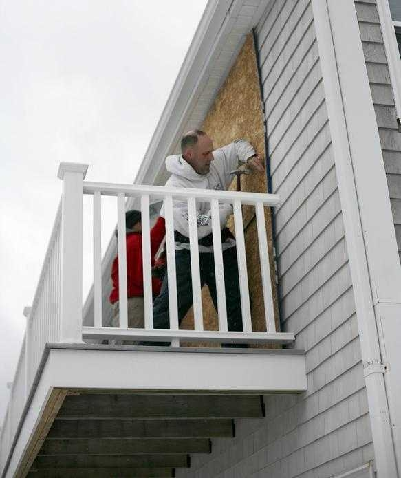 Carpenters Ronnie Davis and Steve Legere of M3 Roofing in Weymouth board up large sliding windows on a waterfront home in Scituate on Oceanside Drive. Monday Jan. 26 , 2015.