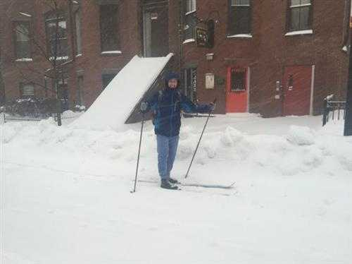 A man straps on his skis to make his way up Massachusetts Avenue in the South End Tuesday morning.
