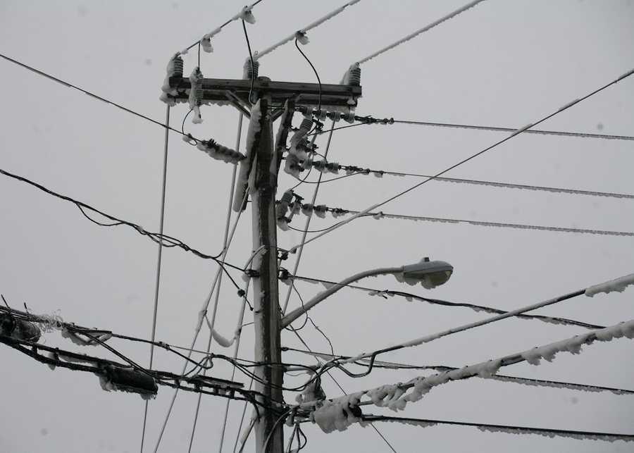 Snow and ice covers utility poles resulting in power outages on Tuesday, January 27, 2015.