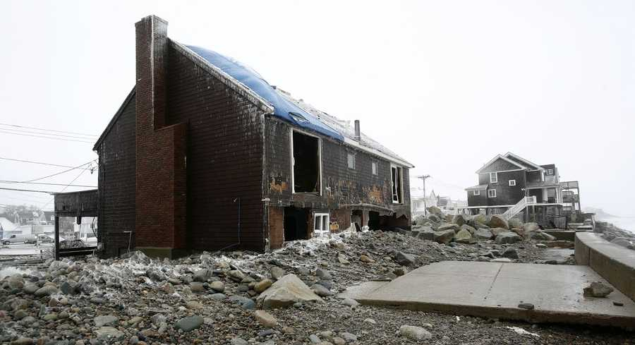 Homes are damaged in Marshfield after parts of a seawall collapsed during the blizzard on Tuesday, January 27, 2015.