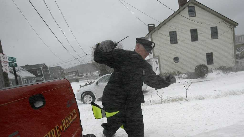 A Scituate police officer tries to walk through the snow during a blizzard on Tuesday, January 27, 2015.