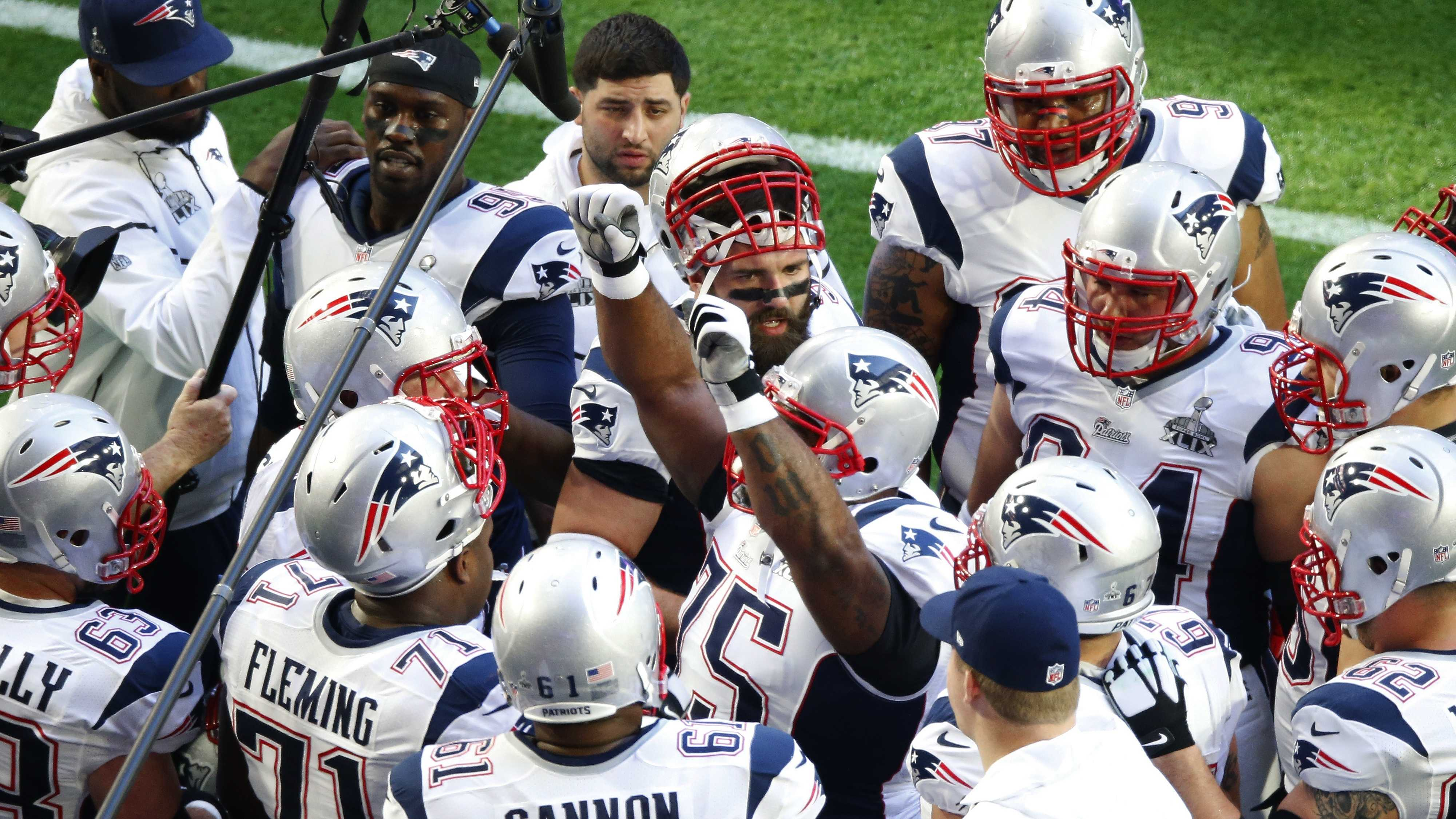 New England Patriots team members huddle before the NFL Super Bowl XLIX football game against the Seattle Seahawks, Sunday, Feb. 1, 2015, in Glendale, Ariz.