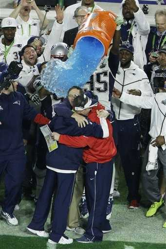 New England Patriots head coach Bill Belichick is dunked with water on the sidelines.