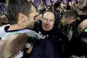 New England Patriots quarterback Tom Brady (12) and head coach Bill Belichick embrace.