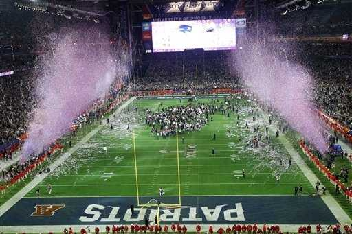 The New England Patriots and media stand on the field after the second half of NFL Super Bowl XLIX football game.