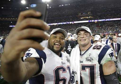 New England Patriots guard Marcus Cannon (61) takes a selfie with Rob Gronkowski (87)