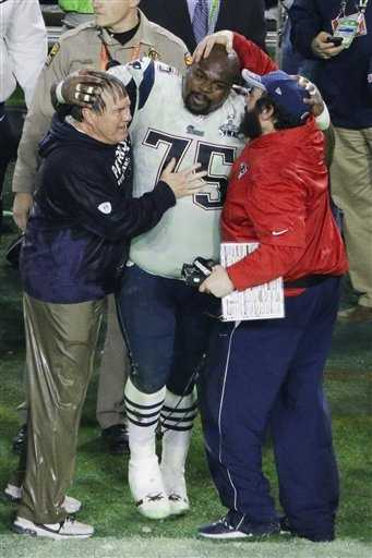 New England Patriots head coach Bill Belichick stands with New England Patriots defensive tackle Vince Wilfork