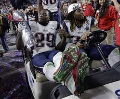 New England Patriots running back LeGarrette Blount (29) holds the Vince Lombardi Trophy as he celebrates with his teammates