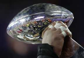 A New England Patriots player holds up the Vince Lombardi Trophy
