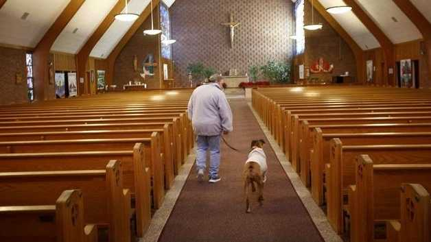 St. Frances Xavier Cabrini Church parishioner Heather Santosuosso of Scituate walks through the church Sunday, Feb. 8, 2015, with her dog Cabrini during Santosuosso's vigil shift.