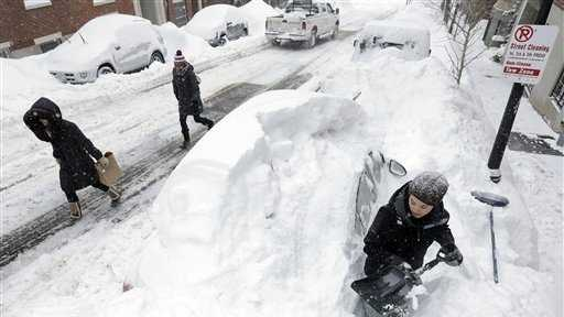 Taylor LaBrecque digs her car out of a snow pile on Beacon Hill.