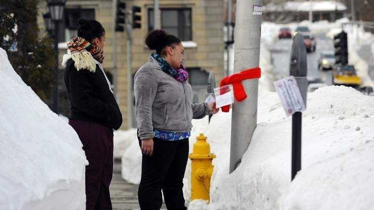 Olivia Nieves of Worcester reads the note attached to a scarf tied to a pole on Irving Street on Tuesday. At left is her friend Jackelina Martinez of Worcester.