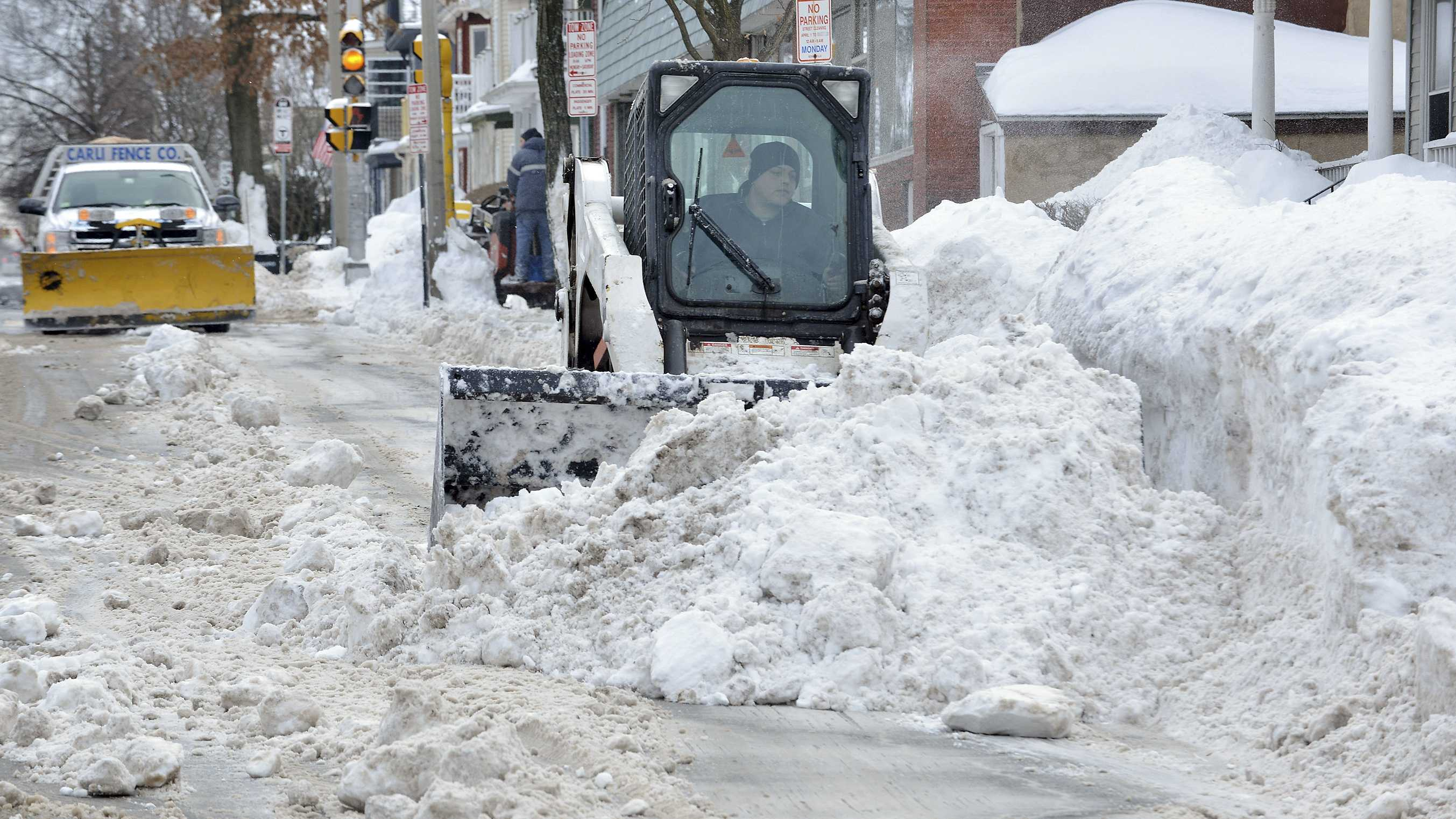 A worker uses a compact front-end loader to clear snow from a road to be removed by a dump truck near Davis Square in Somerville