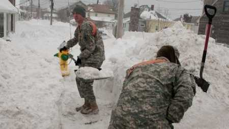 Pfc. Charles Roaf, a Soldier from Methuen, Mass., with the 181st Engineer Company, and Sgt. Miguel Familla, also from Methuen, shovel snow away from a fire hydrant here on Nantasket Avenue Feb. 11.