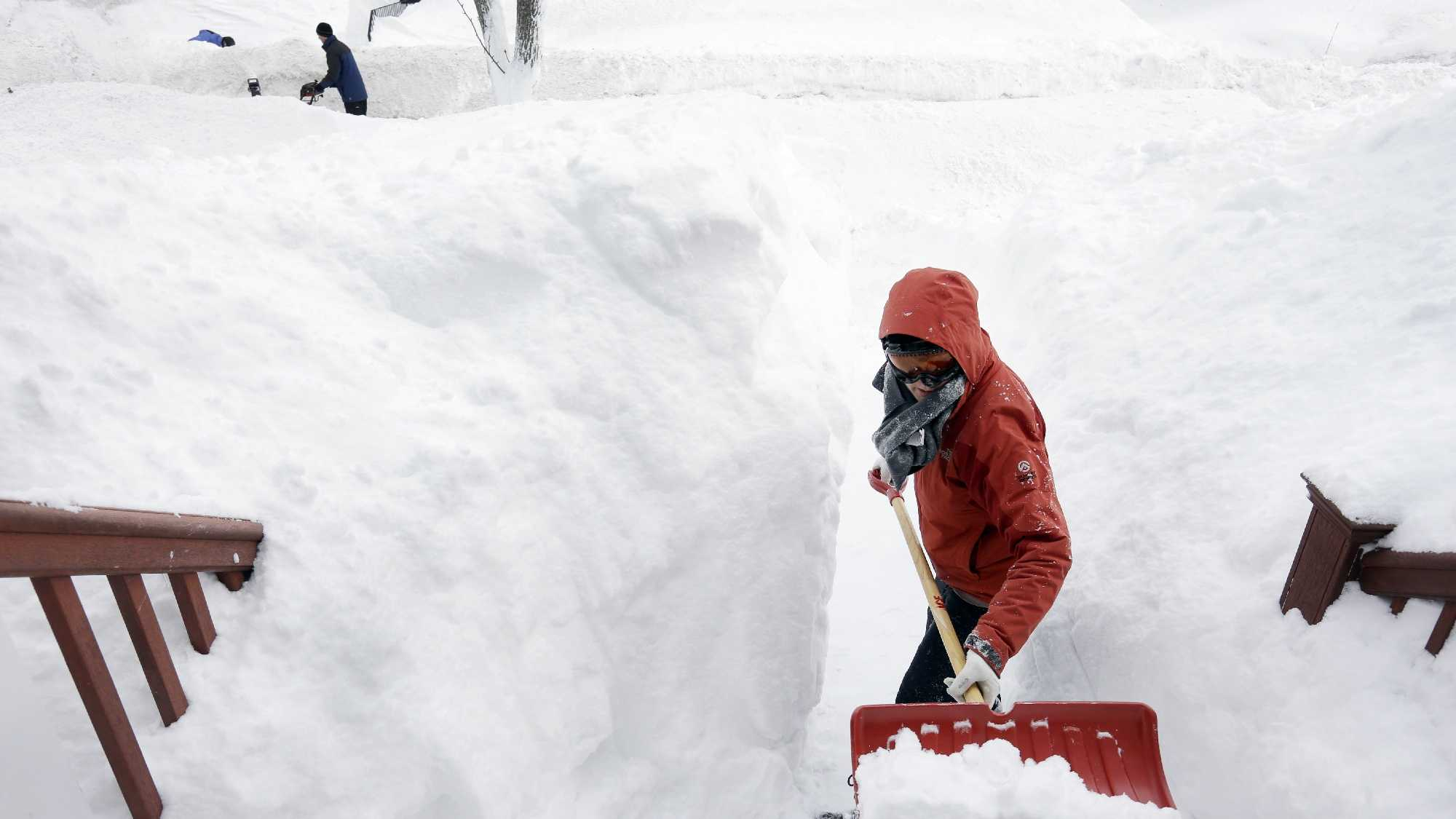 Kim Taylor, of Norwood, Mass., right, shovels a path in the snow in front of her home Sunday, Feb. 15, 2015, in Norwood. A storm brought a new round of wind-whipped snow to New England on Sunday, threatening white-out conditions in coastal areas and forcing people to contend with a fourth winter onslaught in less than a month.