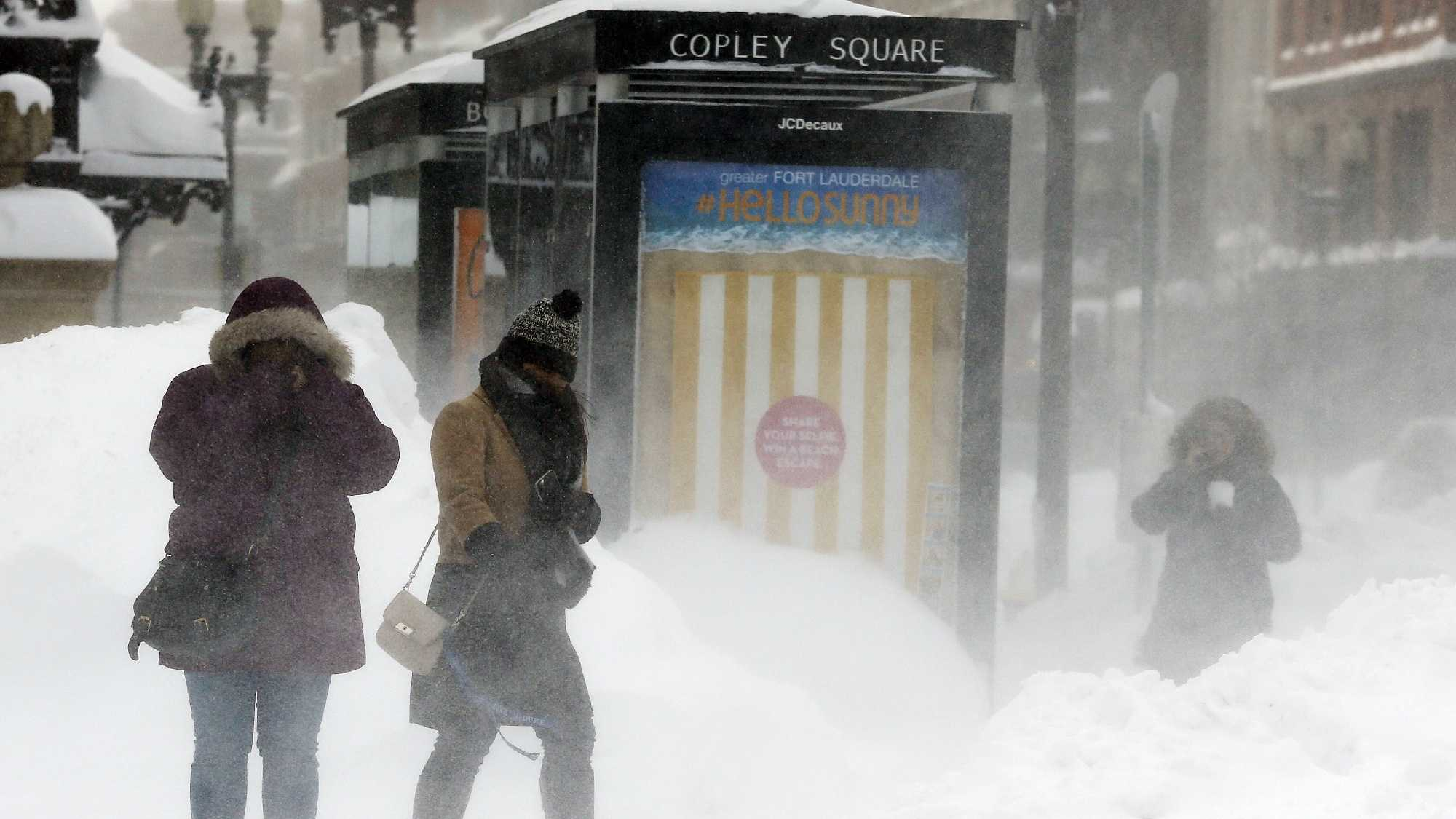 Pedestrians brace against blowing snow in Copley Square in Boston, Sunday, Feb. 15, 2015. A storm brought a new round of wind-whipped snow to New England on Sunday, threatening white-out conditions in coastal areas and forcing people to contend with a fourth winter onslaught in less than a month.