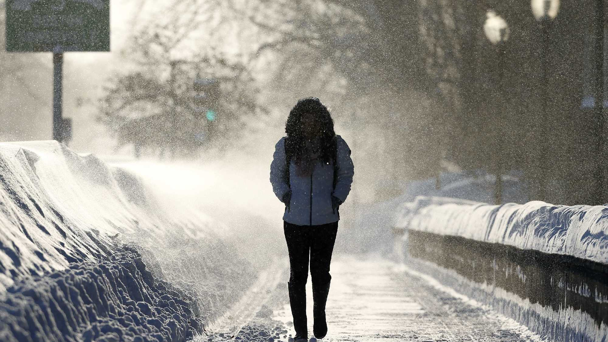 A woman walks through drifting snow in Cambridge, Mass., Sunday, Feb. 15, 2015. A storm brought a new round of wind-whipped snow to New England on Sunday, threatening white-out conditions in coastal areas and forcing people to contend with a fourth winter onslaught in less than a month.