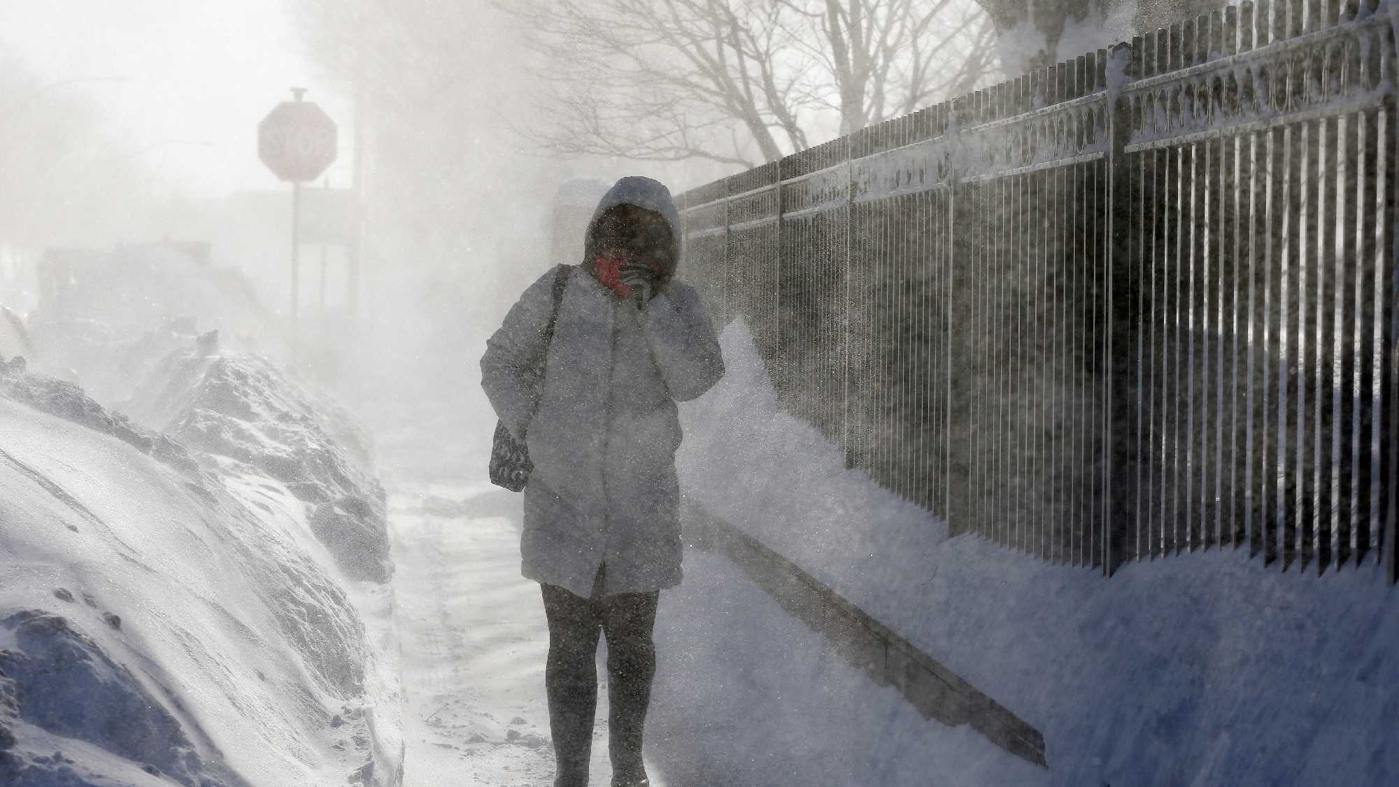 A woman walks through blowing snow in the East Boston neighborhood of Boston, Monday, Feb. 16, 2015. New England remained bitterly cold Monday after the region's fourth winter storm in a month blew through.