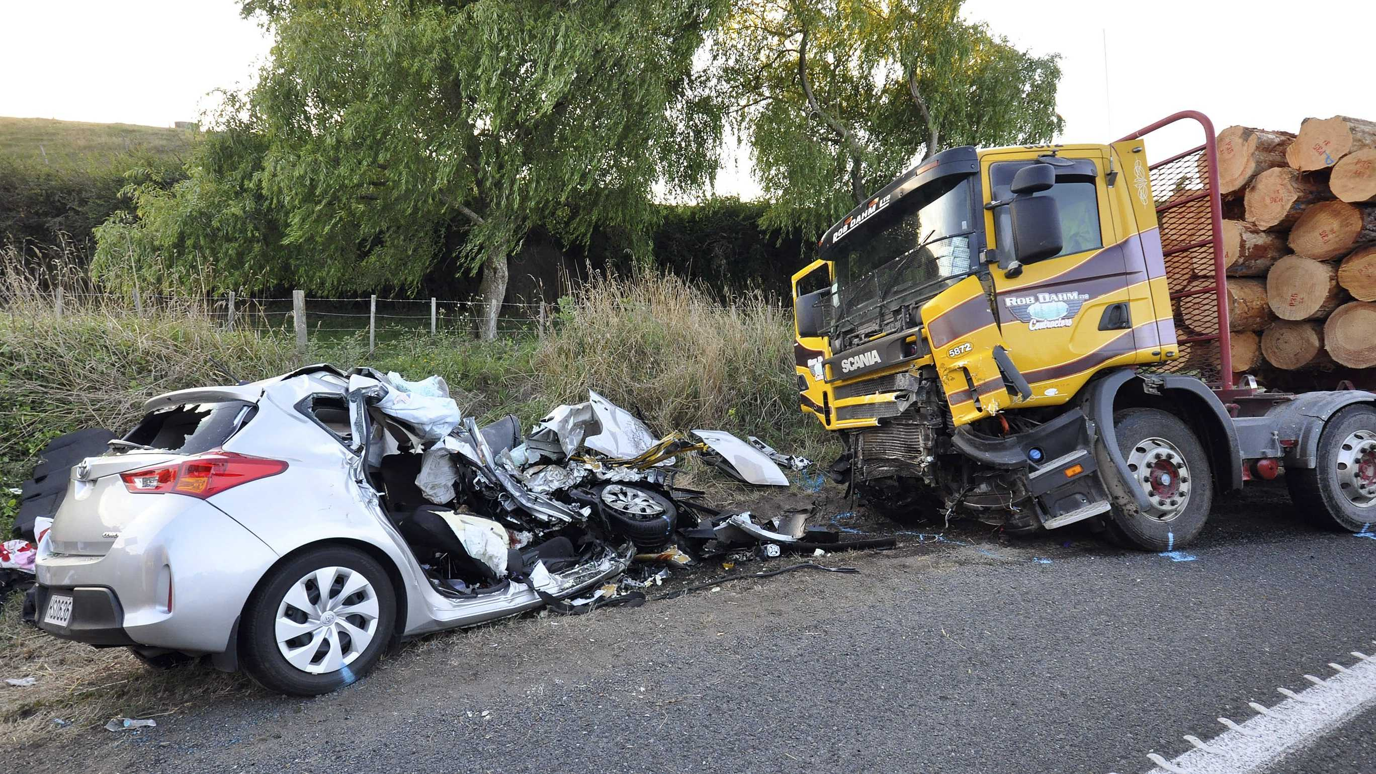 In this Tuesday Feb. 17, 2015 photo, a car and a logging truck sit damaged after they collided head-on near Tokoroa, New Zealand. New Zealand authorities said Thursday, Feb. 19 that U.S. citizens Warren Lee, his wife Aesoon Lee and the couple's daughter, Julia Lee were killed and their son critically injured when their car crashed into the logging truck.