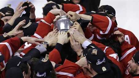 Boston University players reach for the Beanpot trophy after a win against Northeastern in the college hockey Beanpot Tournament's championship game in Boston.