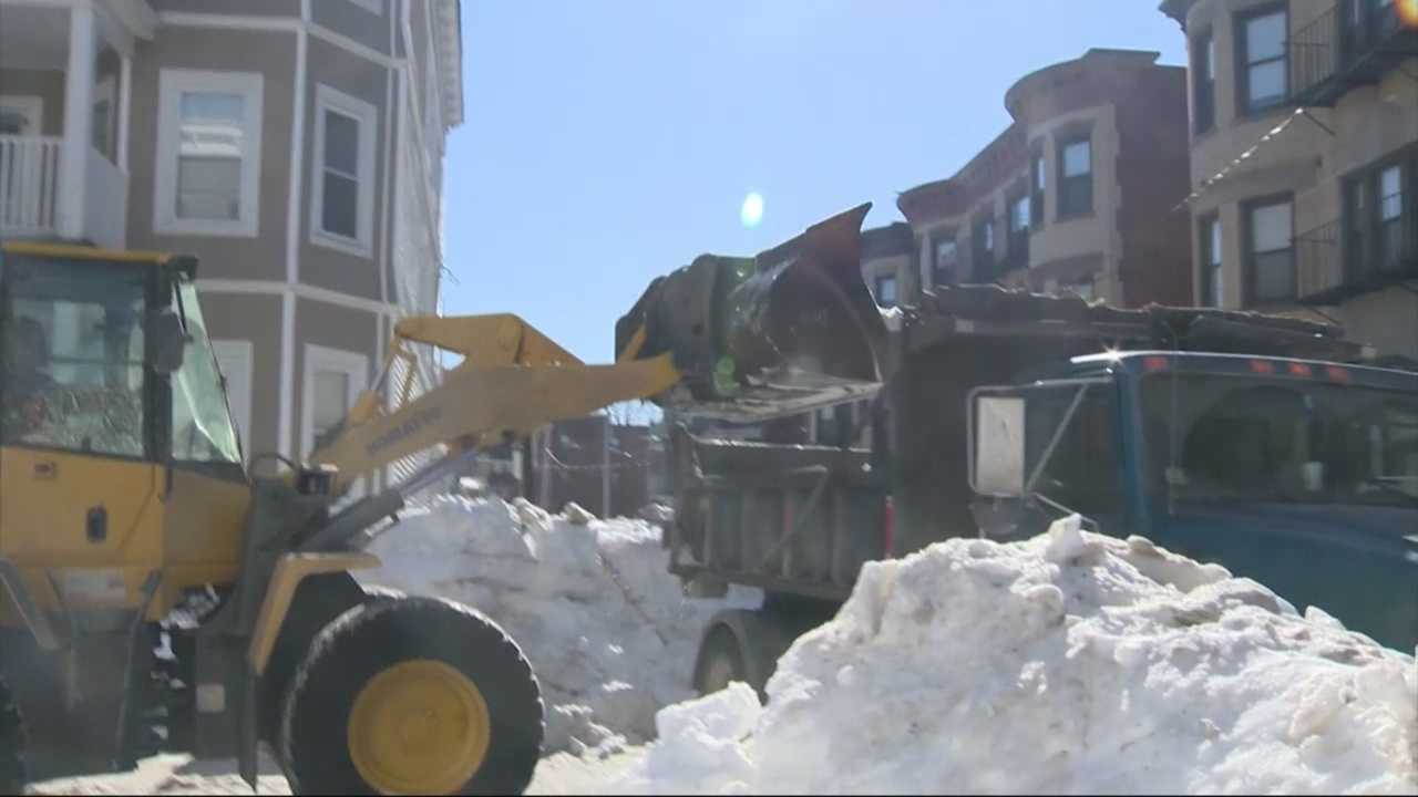 A Dorchester homeowner who watched as city workers dumped a giant mound of snow and ice into her back yard last week watched happily Saturday as that snow was removed.