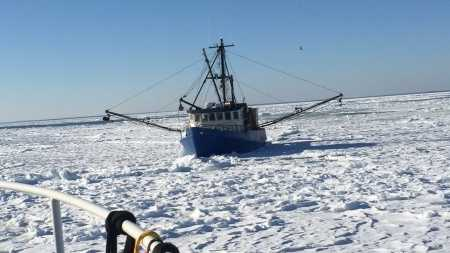 A Coast Guard aids to navigation team from Woods Hole, Mass., assists the fishing boat Capt. RM Chase in Woods Hole on Feb. 28, 2015. The fishing boat became lodged in ice on their way back to New Bedford, Mass., from a fishing trip.