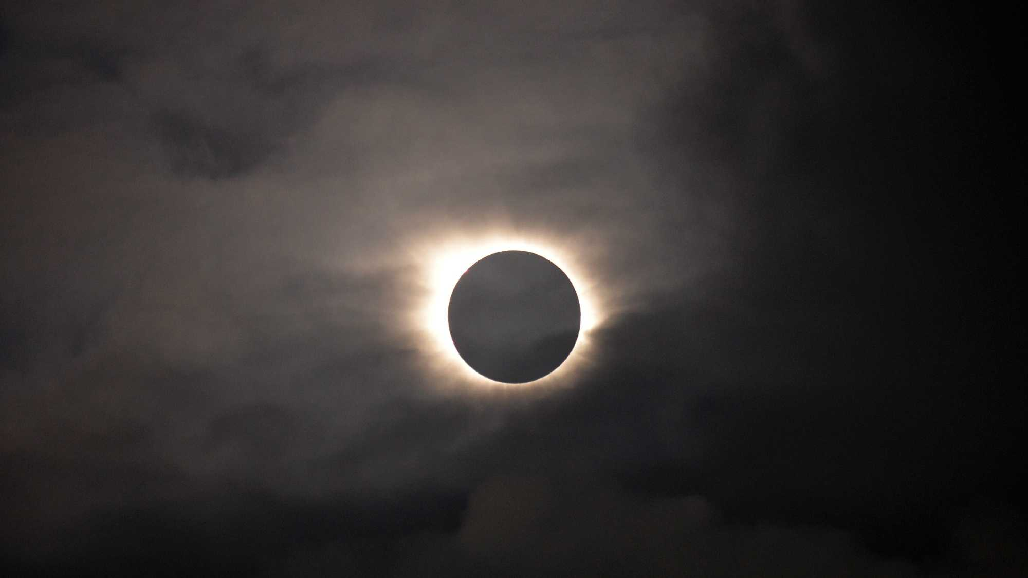 A total solar eclipse is visible through the clouds as seen from Vagar on the Faeroe Islands, Friday, March 20, 2015.  Apart from a few small breaks, a blanket of clouds in the Faeroe Islands blocked thousands of people there from experiencing the full effect of the total eclipse.