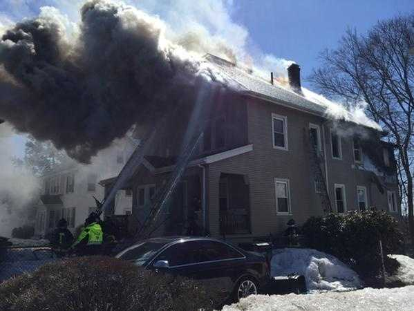 Boston firefighters are battling a two-alarm fire at a West Roxbury house Sunday afternoon.