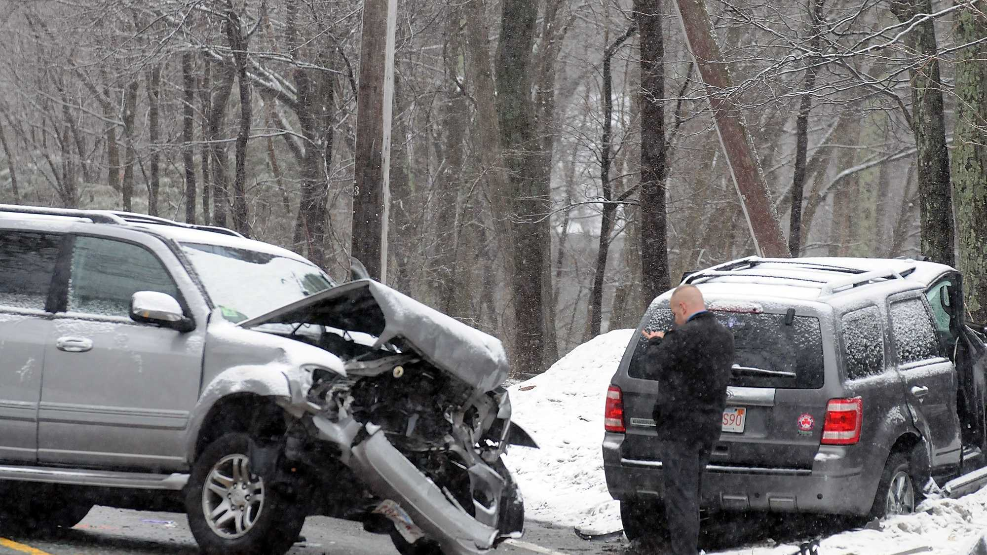 An investigator photographs the scene on Milford Street in Upton. Drunken driving is being blamed for the crash.