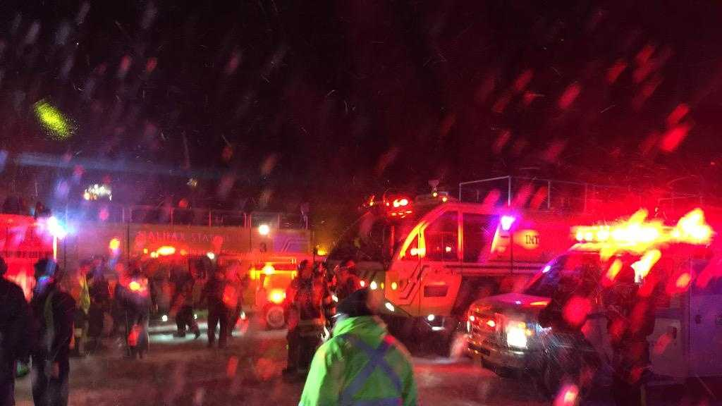 Fire trucks and an airport shuttle are on the scene at the Halifax International Airport early Sunday March 29, 2015 after an Air Canada flight from Toronto made an abrupt landing and left the runway in bad weather.