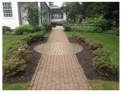 Eye-catching brick and granite walkways meander through beautifully planted gardens.