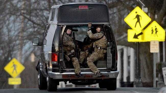 Police in tactical gear drive up to the Hopkinton Public Library to investigate a report of a man who said he had a bomb and two hostages Saturday. The incident turned out to be a hoax.