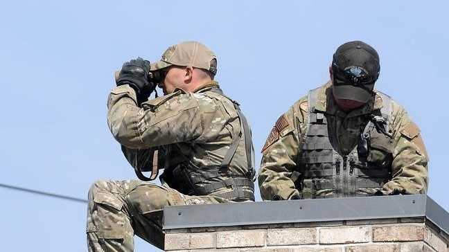 Mass. State Police keep an eye on the scene from the roof of the Middlesex Savings Bank during the 2014 Boston Marathon in Hopkinton.