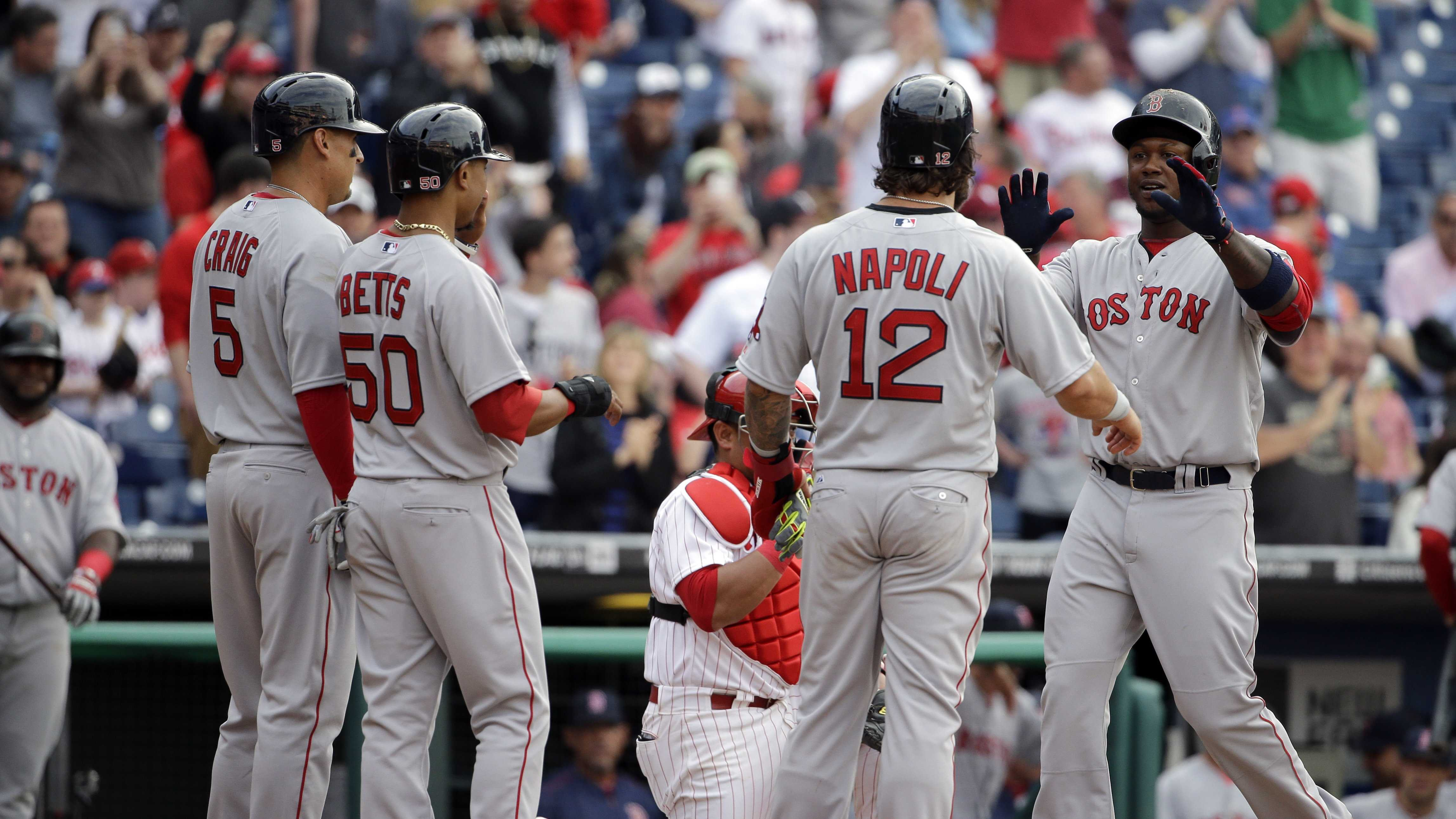 Boston Red Sox's Hanley Ramirez, right, is congratulated by teammates Allen Craig (5), Mookie Betts (50), and Mike Napoli (12) after hitting a grand slam during the ninth inning of an opening day baseball game against Philadelphia Phillies on Monday, April 6, 2015, in Philadelphia. Red Sox won 8-0.